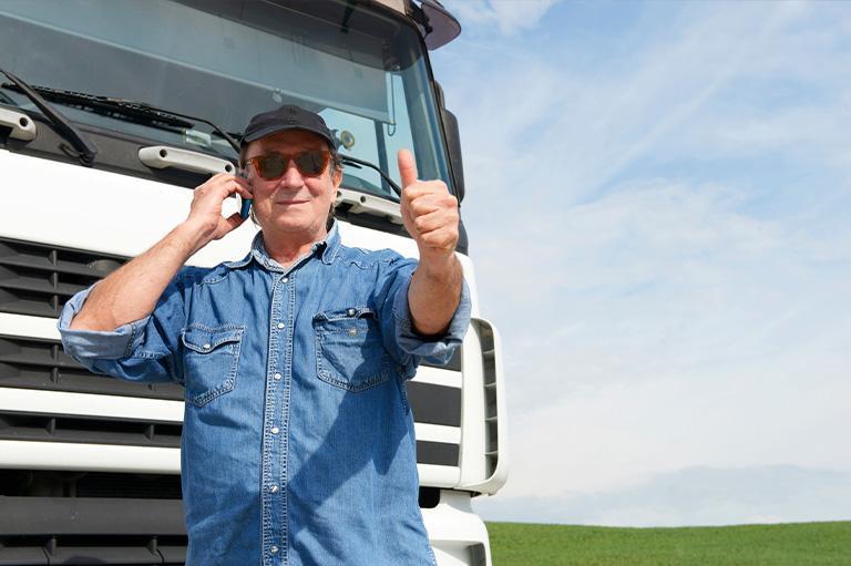 Uśmiechnięty kierowca rozmawiający przez telefon